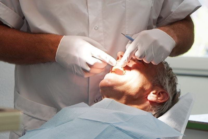 Man at the dentist, having his teeth checked.