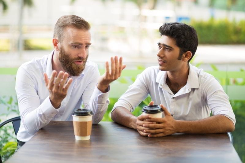 Two male friends drinking coffee and talking in outdoor café