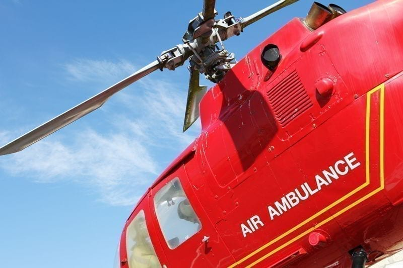 Red helicopter of air ambulance isolated on blue sky background