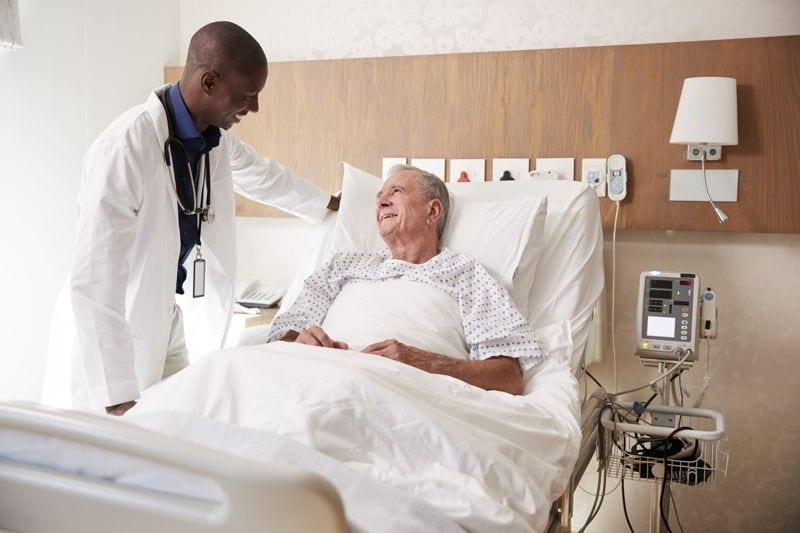 Doctor Visiting And Talking With Senior Male Patient In Hospital Bed.