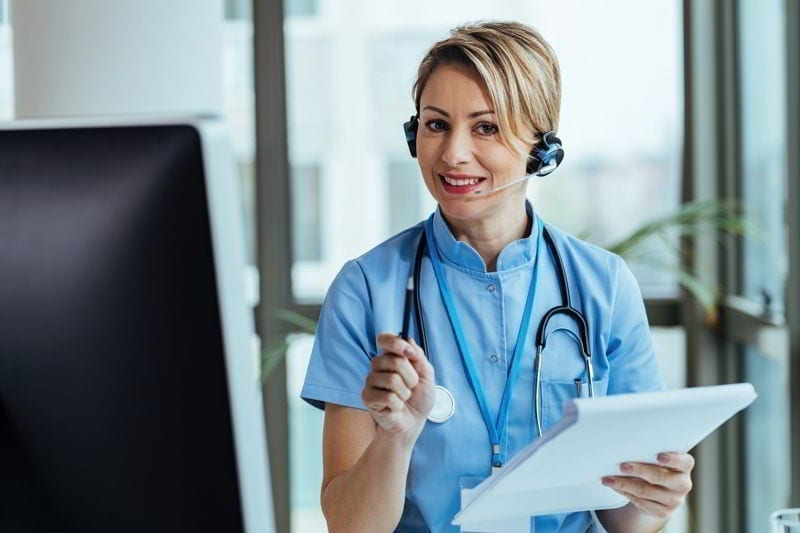 Smiling healthcare worker wearing headset while working at medical call center and talking with patients.