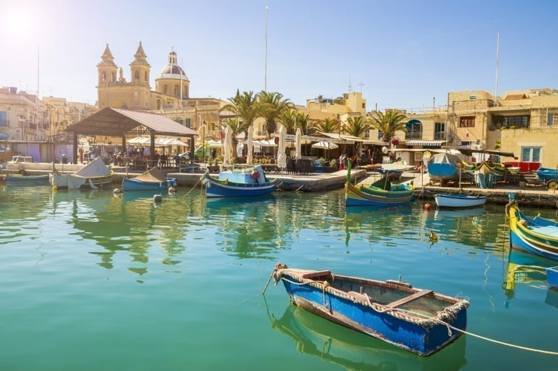 Malta - Marsaxlokk market with traditional colorful Luzzu fishing boats.