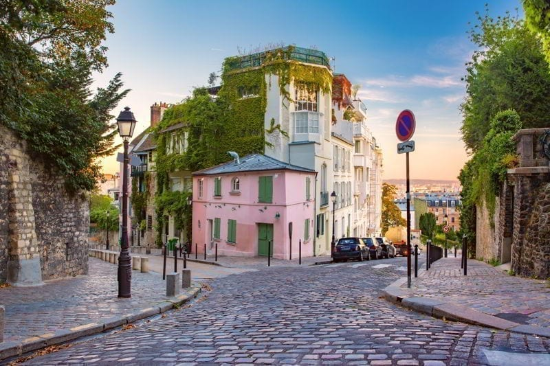 Cozy old street with pink house at the sunny sunrise, quarter Montmartre in Paris, France.