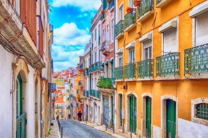 Lisbon, Portugal street perspective view with colorful traditional houses.