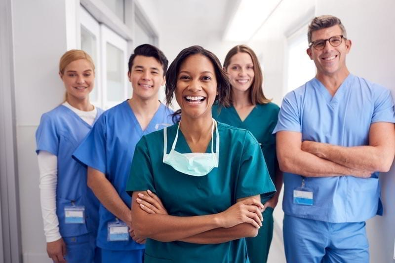 Portrait Of Laughing Medical Team Standing In Hospital Corridor.
