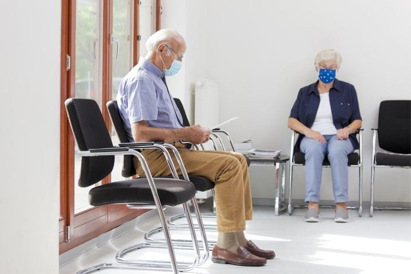 Senior woman and man sitting with face masks in a bright waiting room of a hospital or an office.