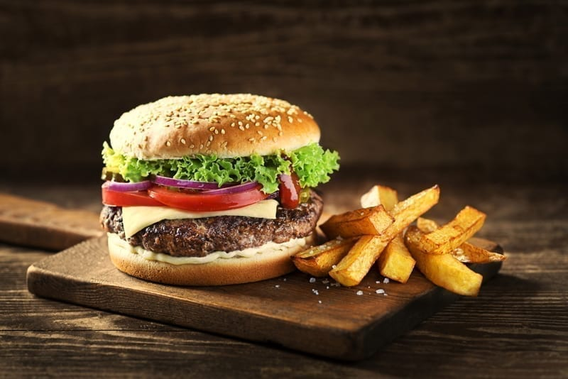 Delicious Hamburger with cheese and french fries on wooden table and dark background.