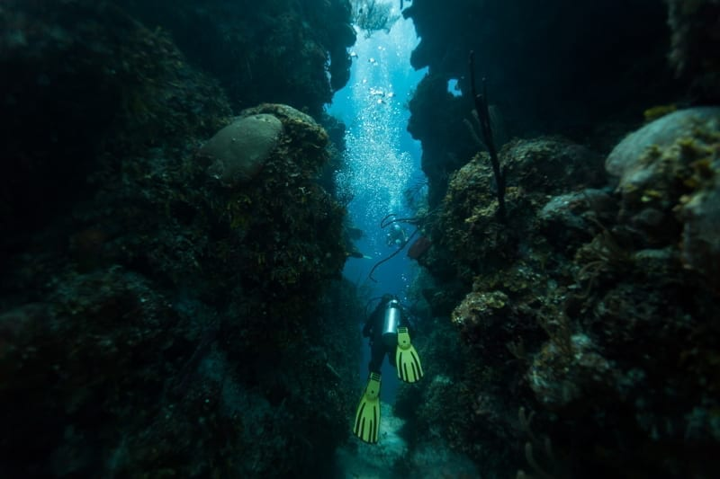 Scuba diver swims through tunnel in Blue Hole Caribbean Sea Belize