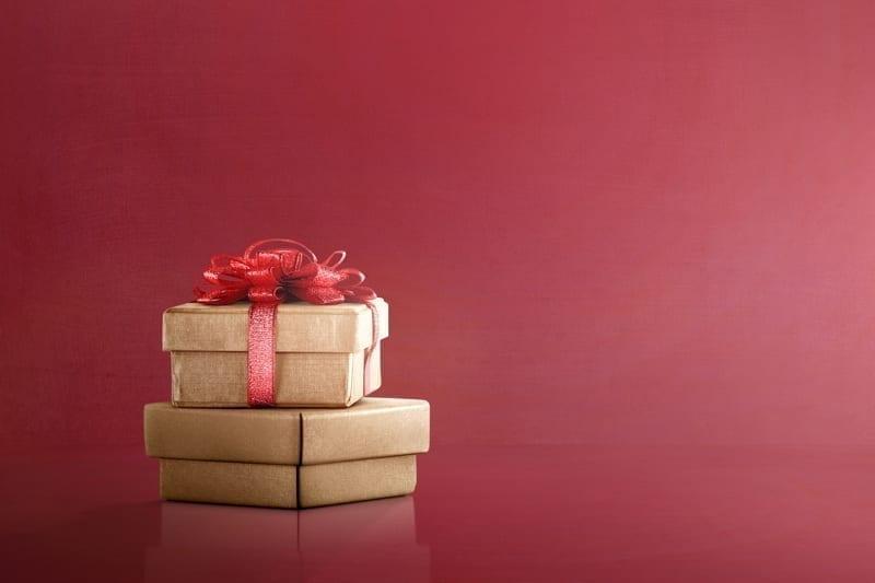 Golden gift box with red ribbon on red background. Boxing Day Concept
