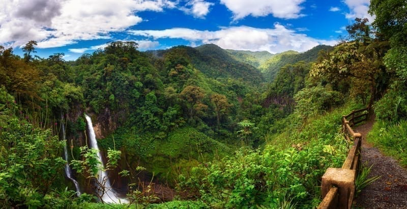 Panorama of the Catarata del Toro waterfall in Costa Rica with surrounding mountains.