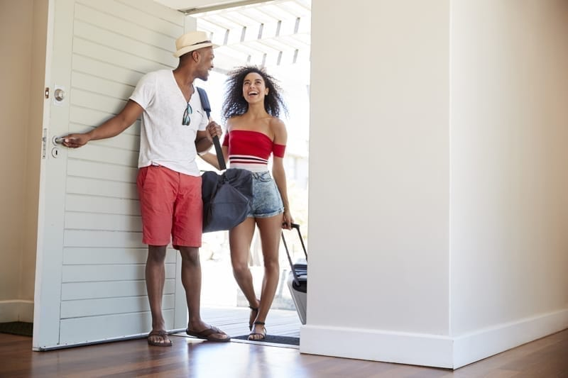 Couple Arriving At Summer Vacation Rental.