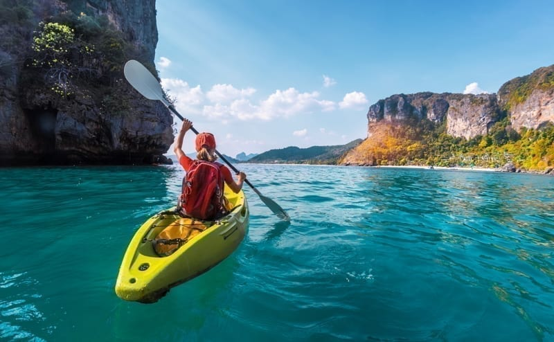 Woman paddles kayak in the tropical sea