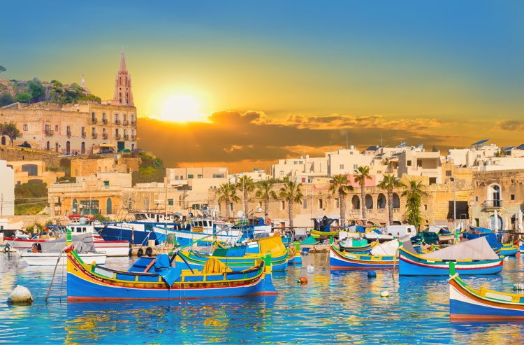Marsaxlokk bay harbour of Malta, with beautiful architecture and boats at dusk