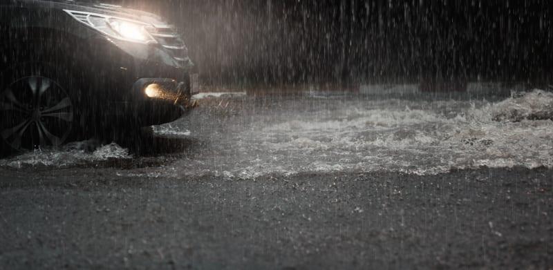 Car with headlights run through flood water after hard rain fall