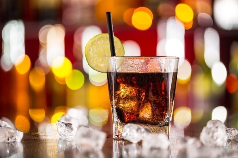 Glass of cola drink on bar counter with ice cubes.