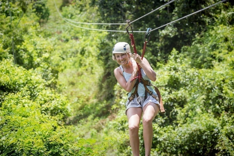 Woman riding a zip line in a lush tropical forest