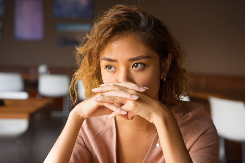 Woman at cafe covering nose and mouth with clasped hands and staring into vacancy.