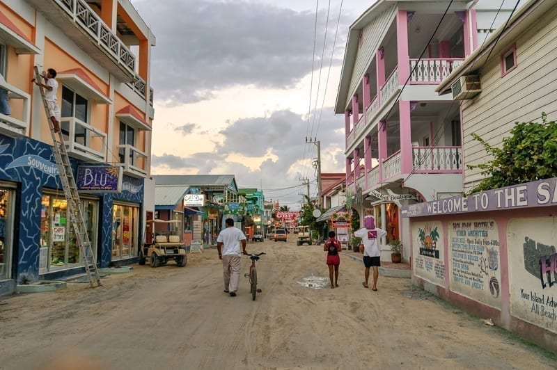 People walk on dirt street in downtown San Pedro island, Belize.