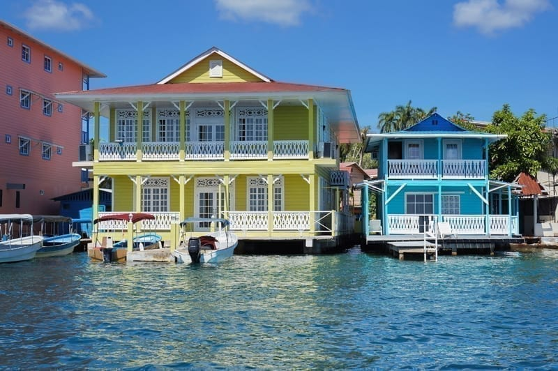 Typical Caribbean colonial homes over the water with boats at dock, Panama.