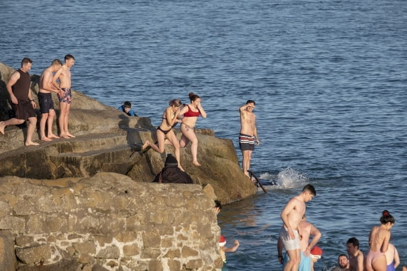 People jumping into the sea at Forty Foot during Christmas traditional swim. Dublin, Ireland.