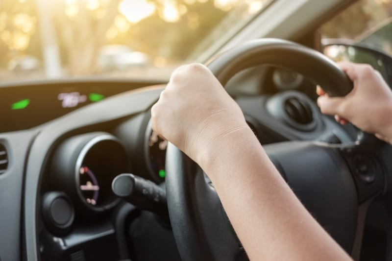 Woman driving her car with both hands on steering wheel.