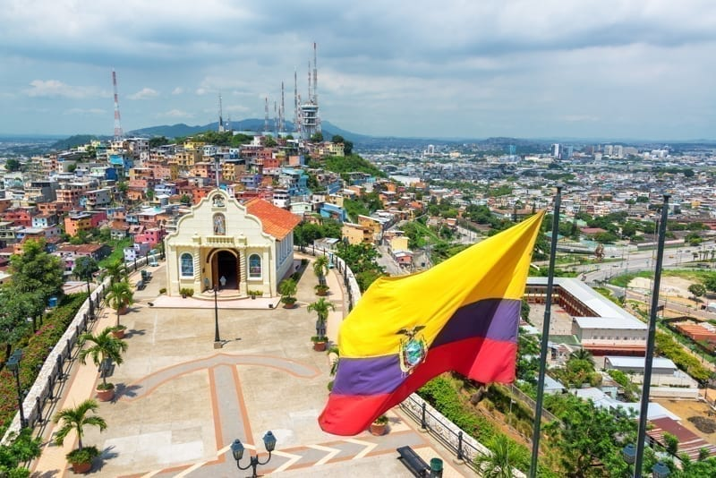 Ecuadorian flag on top of Santa Ana hill with the city of Guayaquil in the background on a cloudy day.