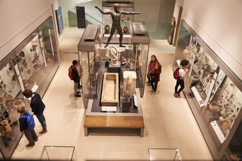 Overhead view of busy museum interior with visitors.
