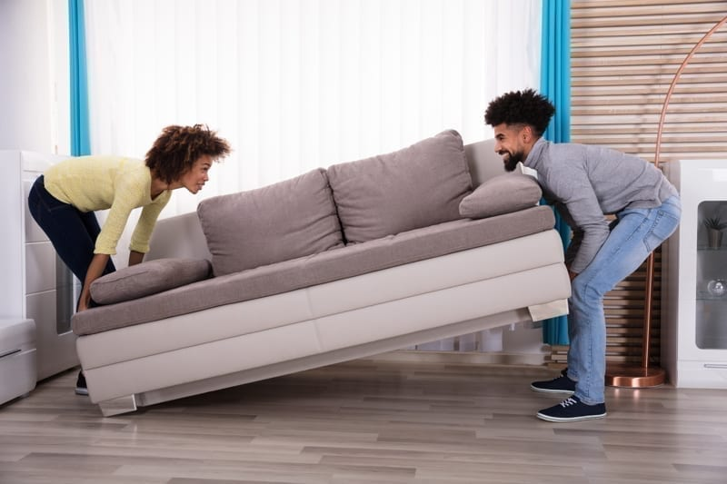 Side View Of Smiling Couple Lifting Sofa In Living Room.