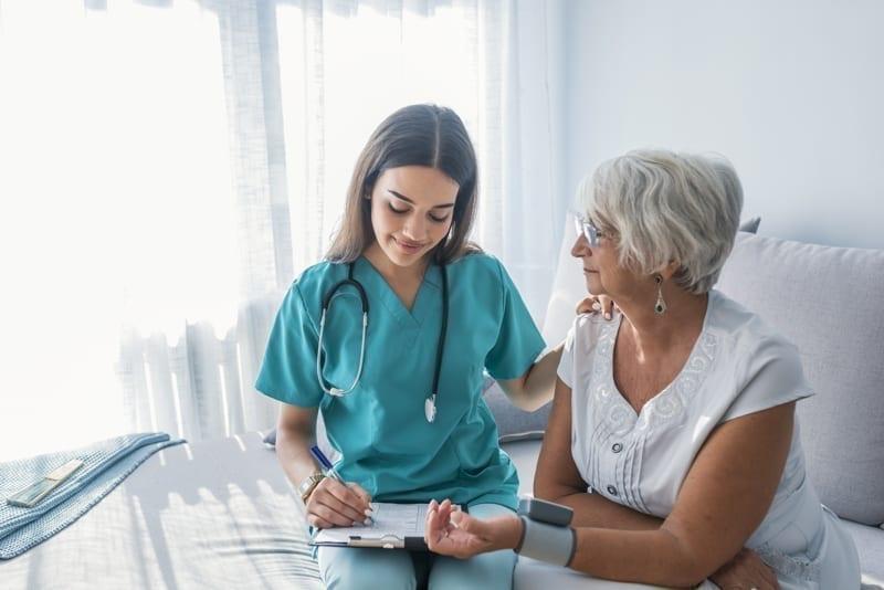 Nurse doing blood pressure monitoring for senior woman.