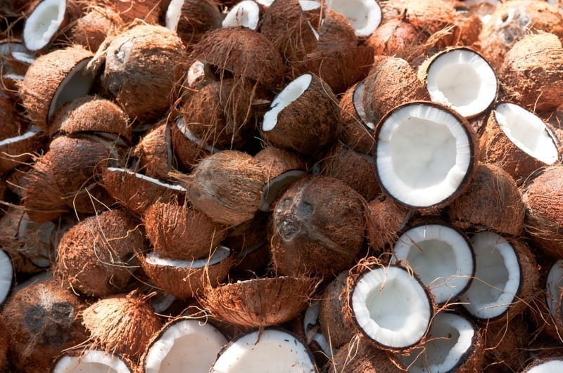 Large pile of Coconuts with one coconut cut open in half.