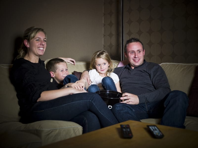 Family in front of The Television sitting in the sofa.