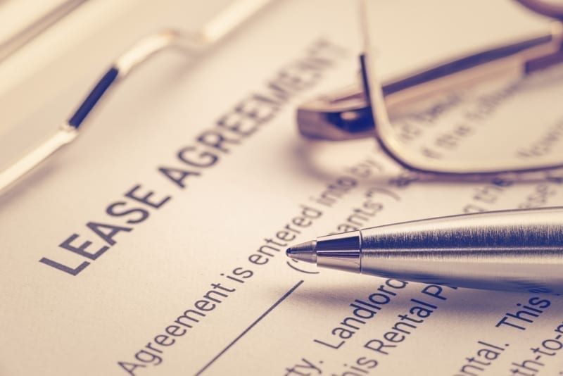 Pen and glasses on a lease agreement form.
