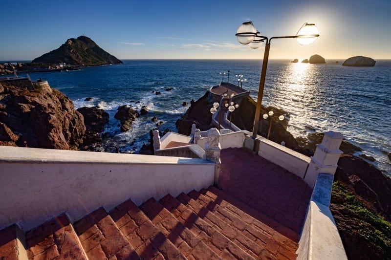 Charming stair case leading down to an overlook with the lighthouse in the background in Mazatlan, Mexico.