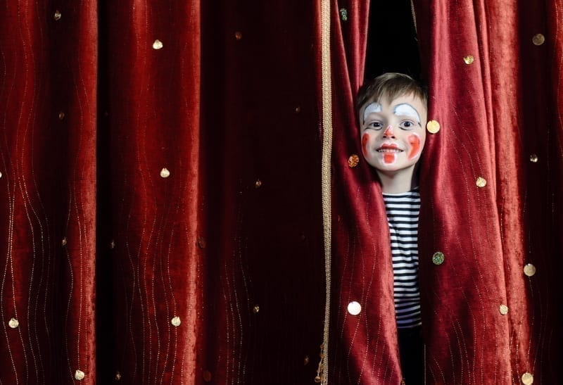 Young Boy Wearing Clown Make Up Peering Out Through Opening in Red Stage Curtains.
