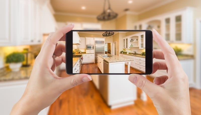 Hands Holding Smart Phone Displaying Photo of Kitchen Behind.