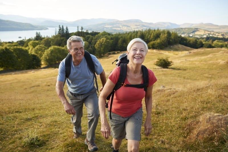 Senior Couple climbing hill on hike.