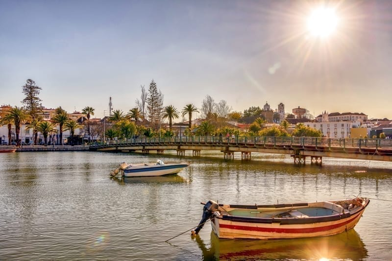 Boats on serene Gilao river and the sun shining over picturesque Tavira