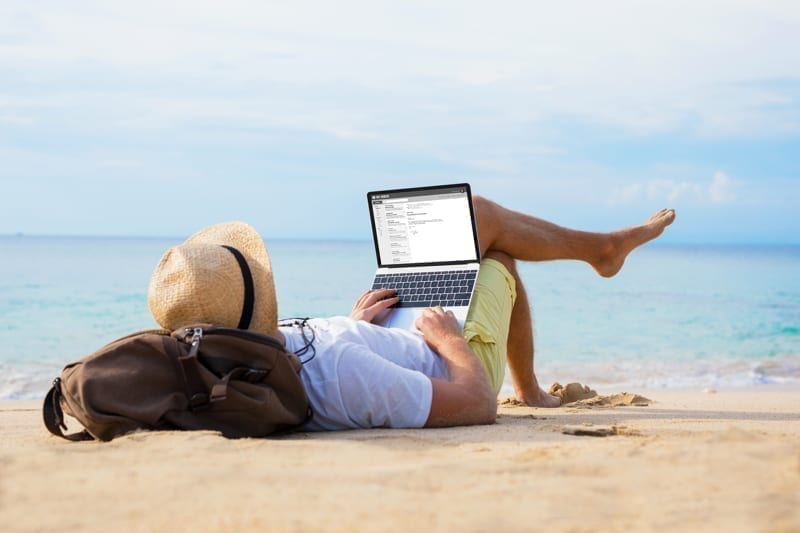 Male writing on laptop while relaxing on beach