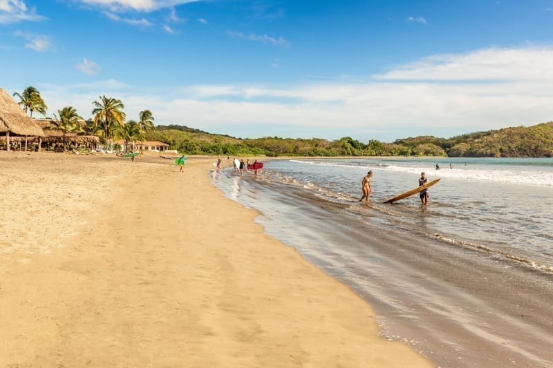 Surfers entering waters at Venao beach in Pedasí, Panama on a beautiful afternoon.
