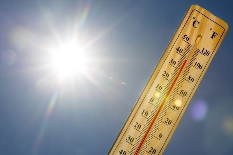 Mercury thermometer marking 39 degrees Celsius 100 Fahrenheit in a sunny day.