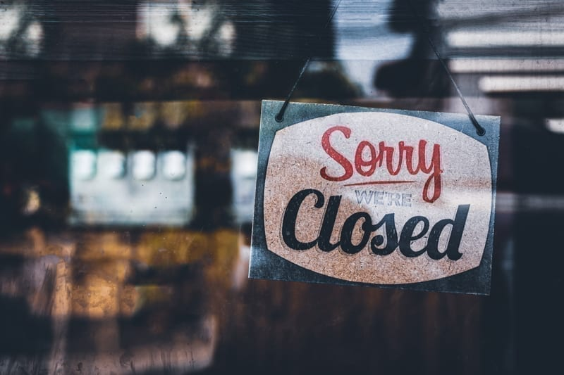 """""""Sorry we're closed"""" sign hanging on a cafe window."""