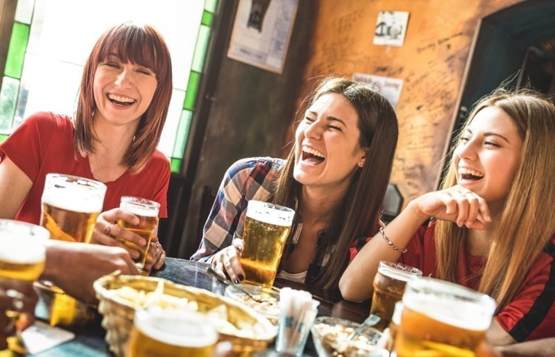 Happy girlfriends women group drinking beer at pub.