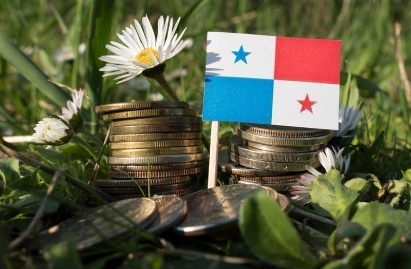 Panama flag with stack of money coins with grass and flowers