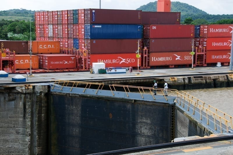 A fully loaded cargo ship filled with containers moves through the Miraflores Locks in the Panama Canal.
