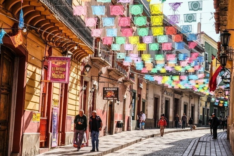 Mexicans walking on cobblestone street with sun lit colorful banner flags hanging above, Guanajuato, Mexico