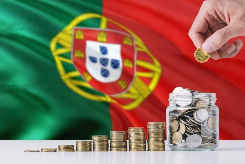 Business man holding coins putting in glass, Portugal flag waving in the background
