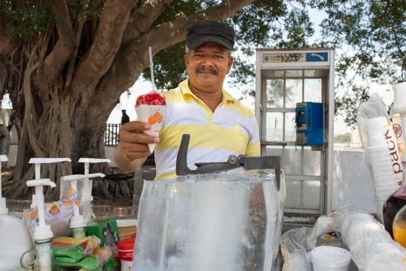 Vendor selling fruit-flavored shaved ice, known as a raspado