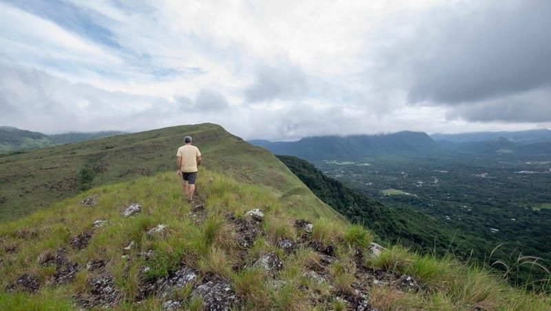 Male hiker walking on top of India Dormida mountain at El Valle de Anton, Panama