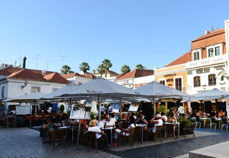 Tourist sitting in an outdoor café in Cascais, Portugal