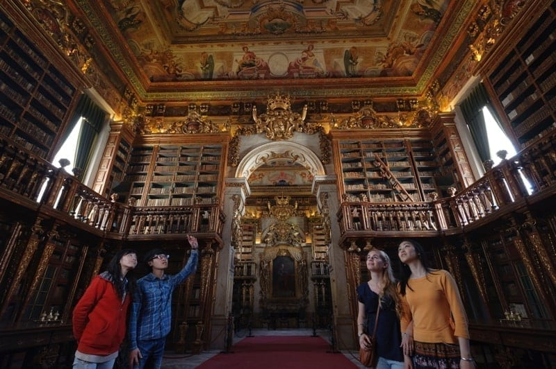 People visiting Coimbra University's 18th century baroque library Biblioteca Joanina in Coimbra, Portugal